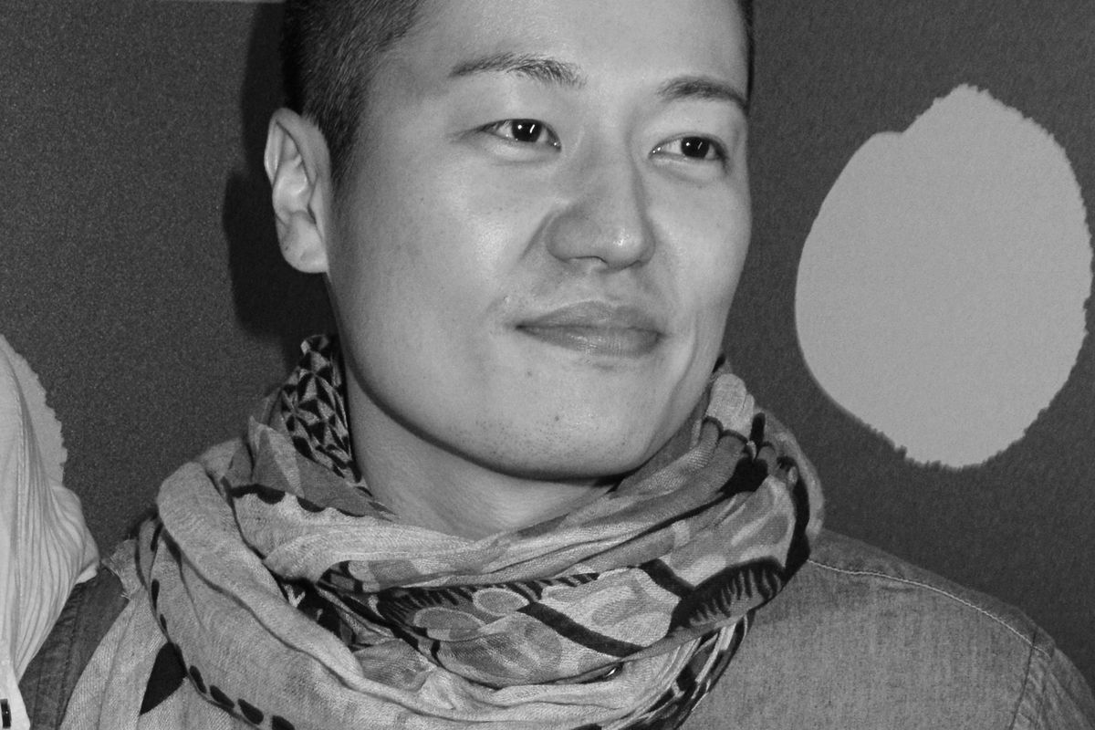 Close-up, black and white photo of a man wearing a scarf.