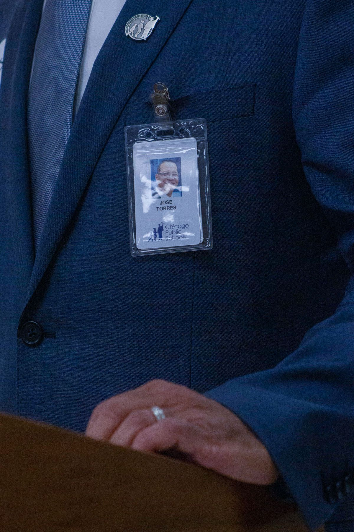 Interim CEO Jose Torres' name badge hangs on the pocket of his suit jacket as he makes a speech during a press conference.