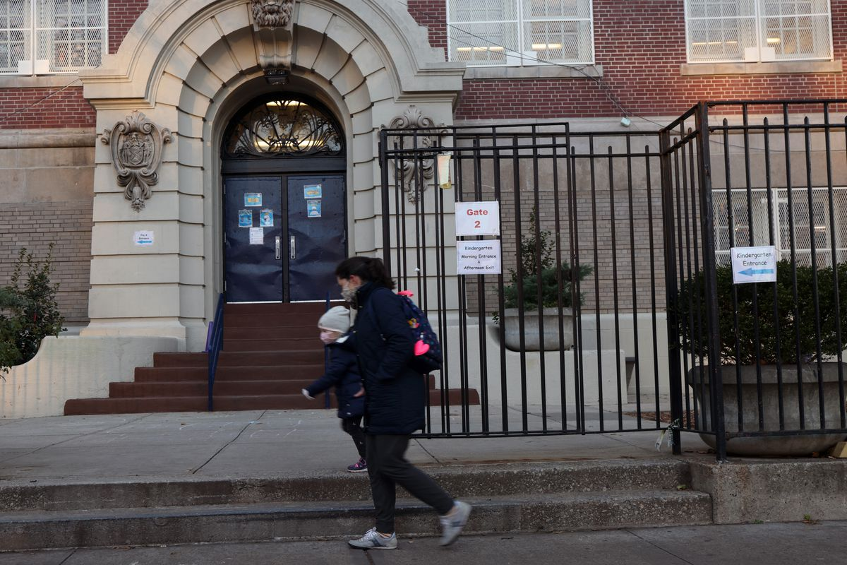 People walk by a public school in Brooklyn on Nov. 18, 2020. Public schools in New York City, the largest school district in the nation, will close again on Thursday, officials have said after the city reached a 3% Covid test positivity rate.