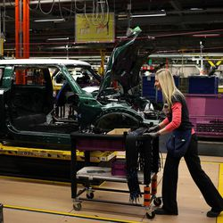 Workers are shown on the assembly line at the BMW Mini Plant Oxford on Nov. 18, 2013.