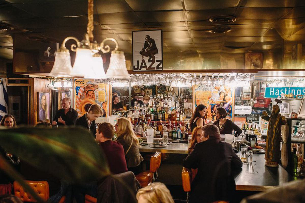 """Customers sit at a well-lit bar inside Cafe D'Mongos Speakeasy below a poster that says """"jazz."""""""