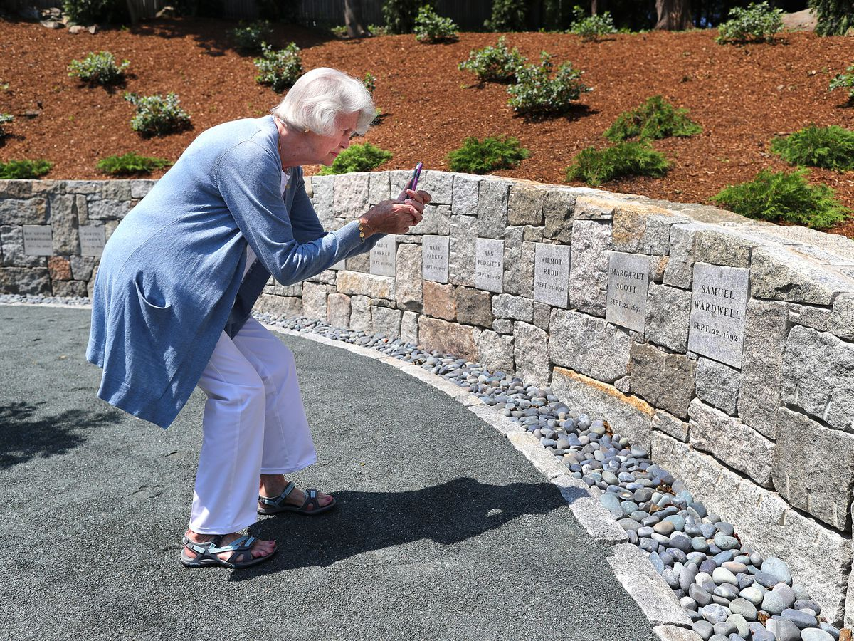 A woman snapping a photograph of a memorial wall.