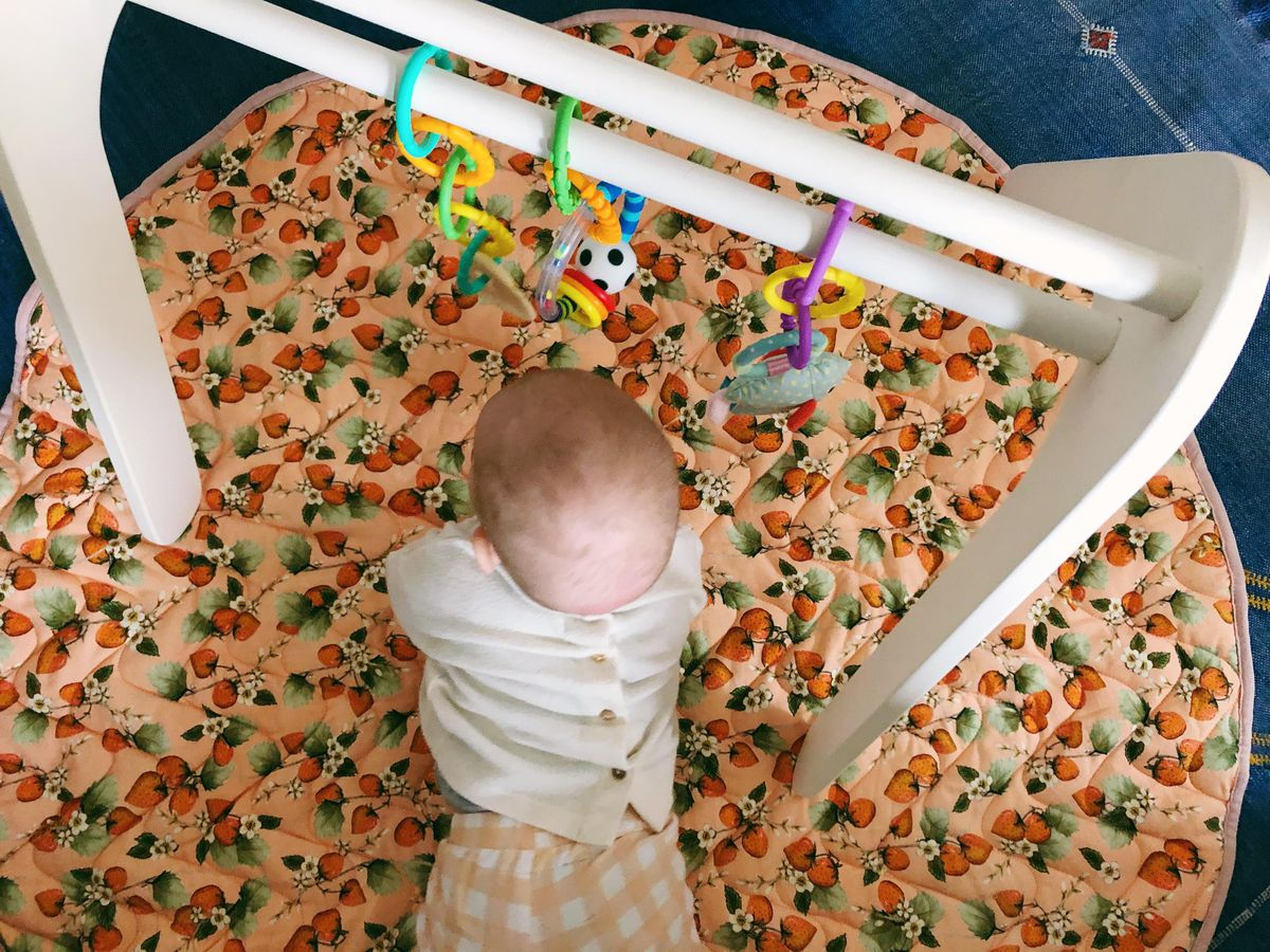 A baby seen from above, playing with toys hanging from a wooden structure.