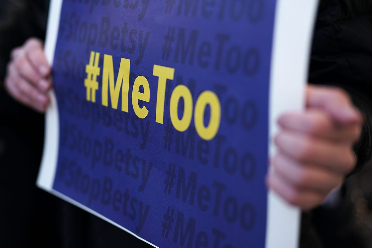 An activist holds a #MeToo sign during a news conference on a Title IX lawsuit outside the Department of Education in Washington, DC, on January 25, 2018.