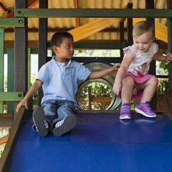 In this Friday, Sept. 7, 2012 photo, Ellyson Hooker is watched over by her adopted brother Daniel as they play together at a restaurant in Guatemala City. Daniel was 18 months old when the Tennessee couple Ryan and Jessica Hooker began the process to adopt him in Guatemala. They just got him at age 6. His is one of hundreds of adoption cases that were put in limbo five years ago, when the Guatemalan government declared a moratorium on international adoptions because of irregularities and fraud.