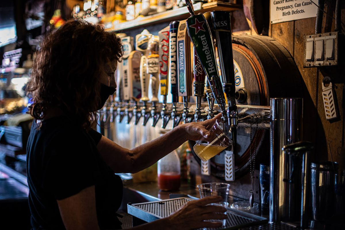 A bartender in a mask pours beer inside of a dive bar.