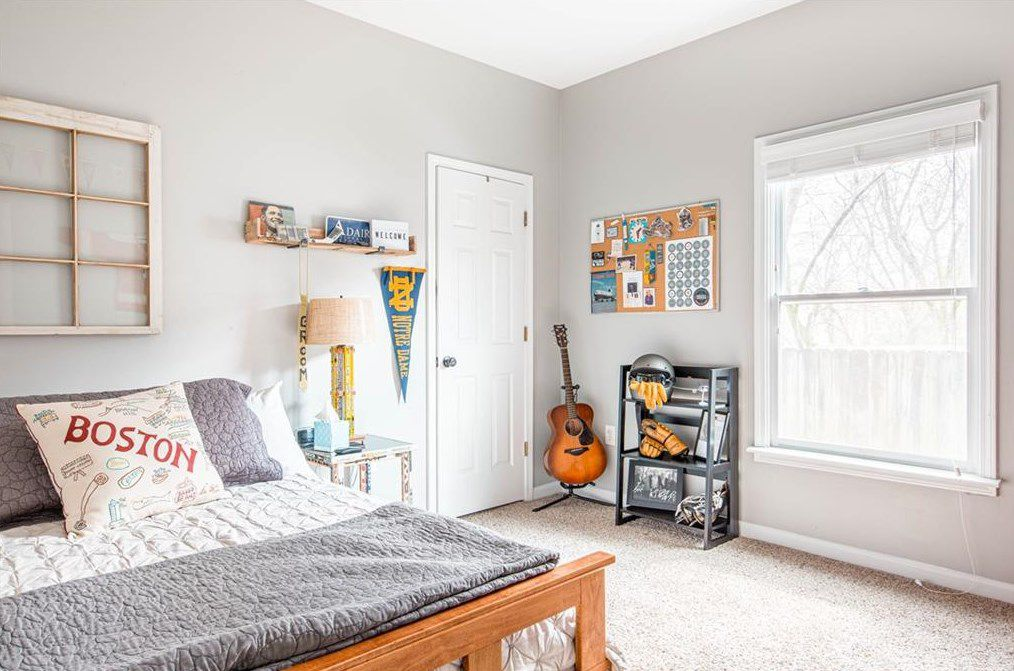A bedroom with thick carpeting and gray walls with a guitar in a corner.