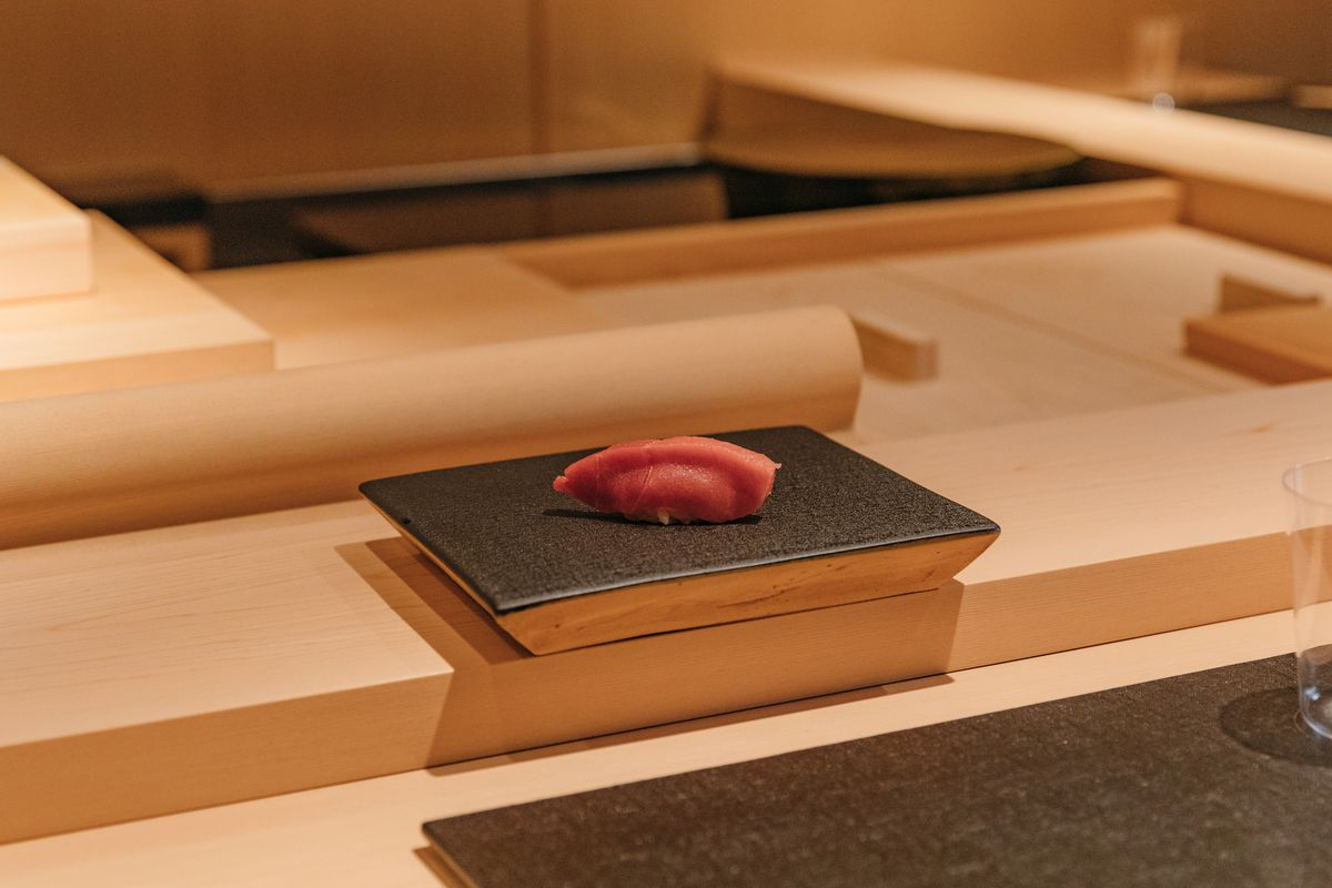 Raw tuna served atop rice plated on a black slate on a wooden counter.