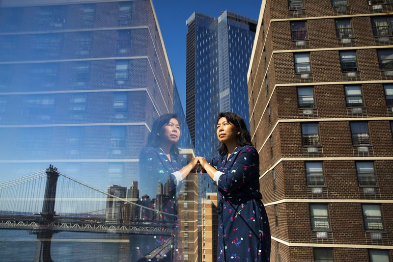 A woman standing on her roof in Chinatown with a new high rise behind her.