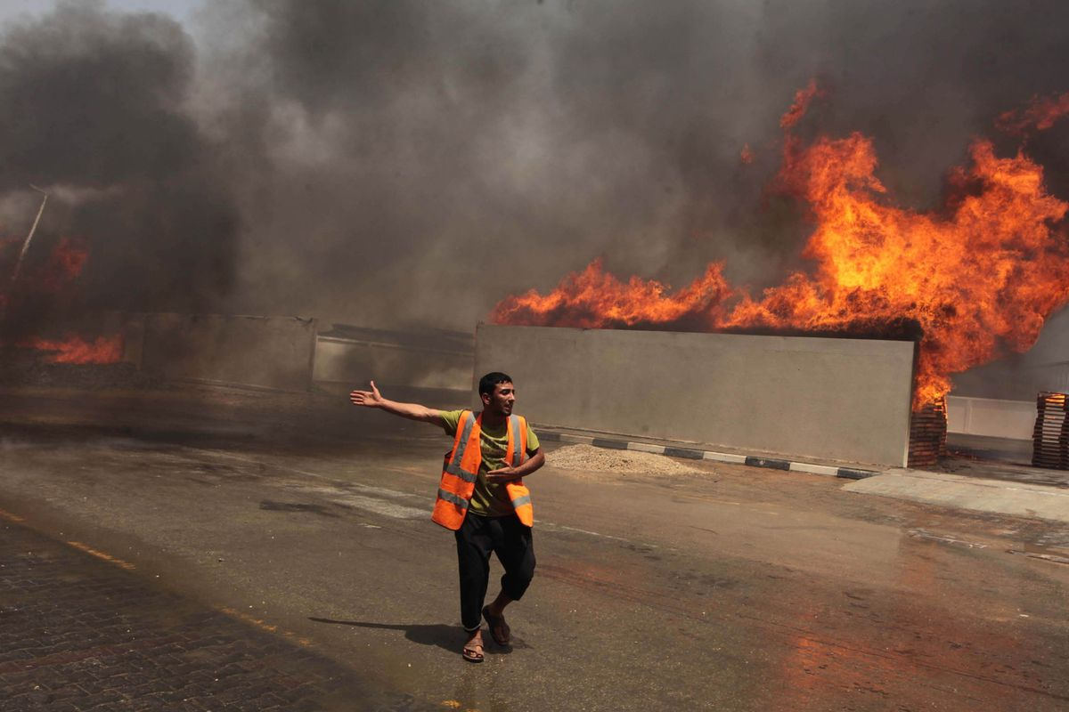 A Palestinian worker at the site of an Israeli air strike in Gaza City