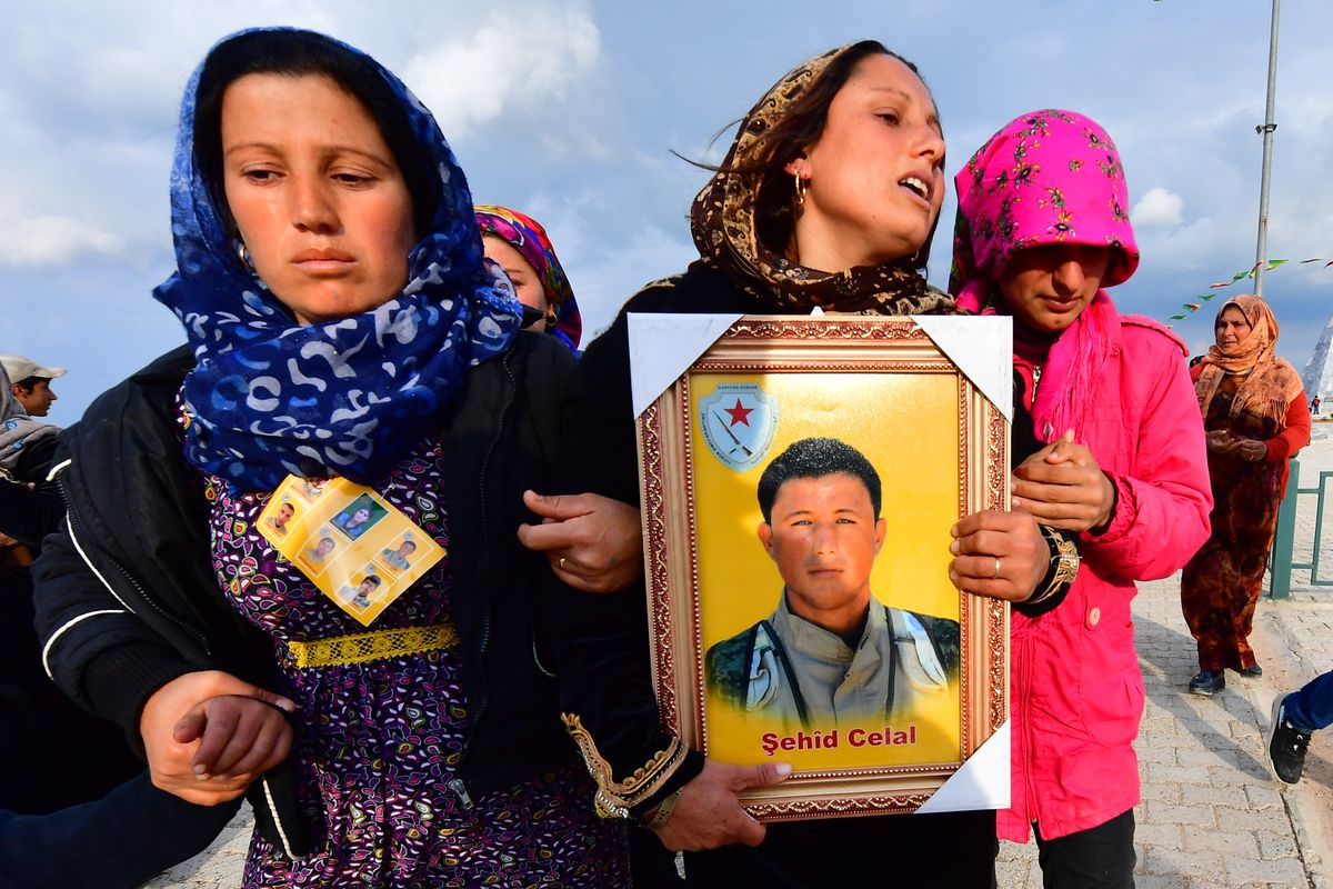 Three crying women carry a portrait during a funeral.