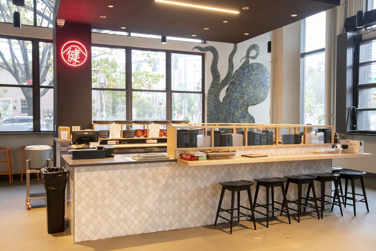 The Ako by Kenaki sushi counter inside the Roost includes a neon sign and a mural of an octopus in the background.