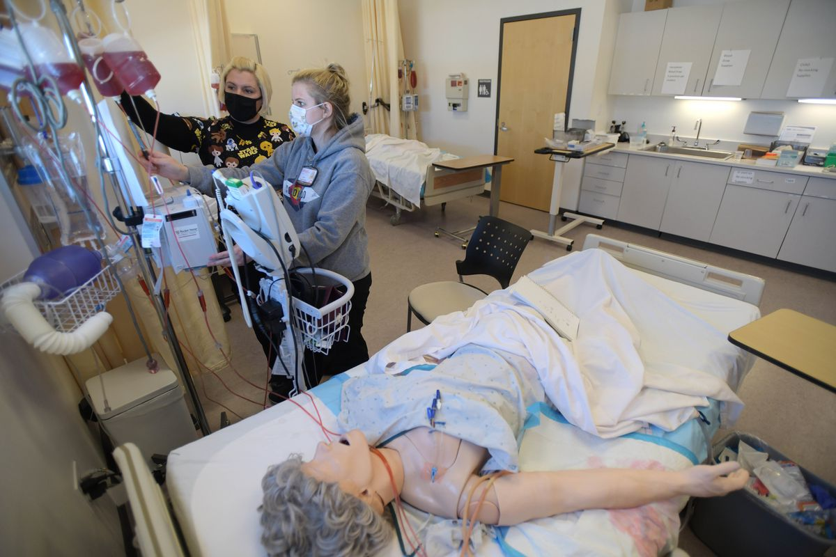 Two masked nursing students, Jade Prophet, left, and Cami Gardetto, stand at a monitor in a nursing simulation classroom at Colorado Northwestern Community College. In the foreground a dummy of a woman lays on a hospital bed, with tubes connecting her to machines.