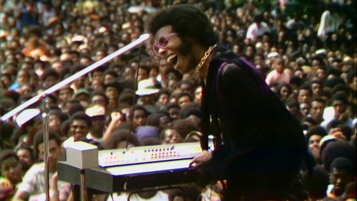 Sly Stone sings into a microphone in front of a keyboard and a crowd.