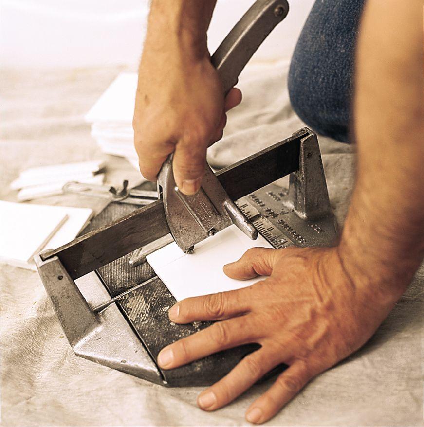 Man Uses Tile Cutter To Cut Bathroom Tile