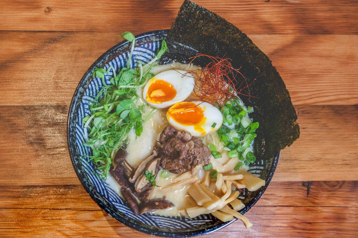 A bowl of oxtail kare kare ramen shot from above, with nori, soft-boiled eggs, pea shoots, spring onions, and shiitake mushrooms
