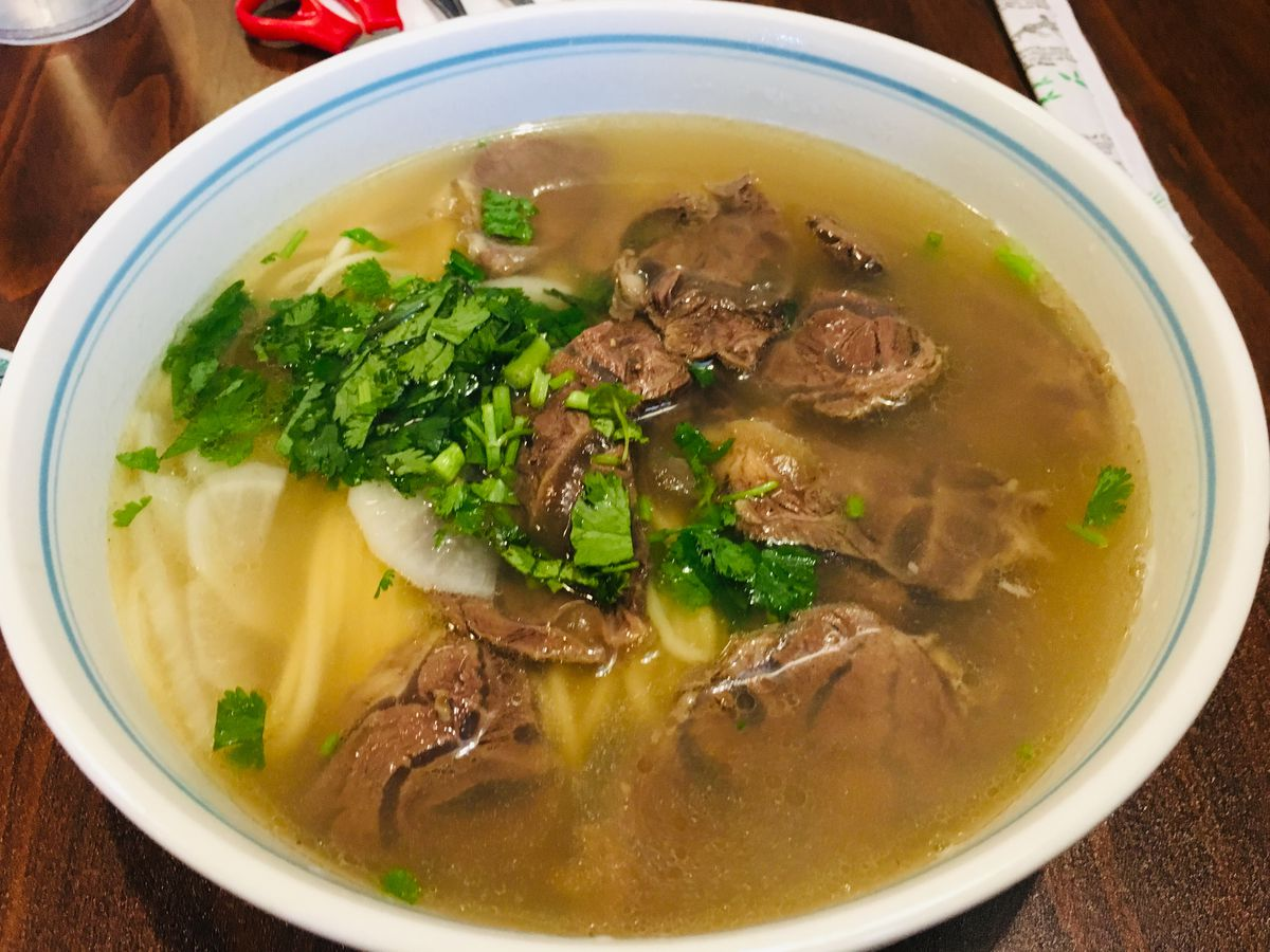 A bowl of beef soup with green garnish sprinkled on top.