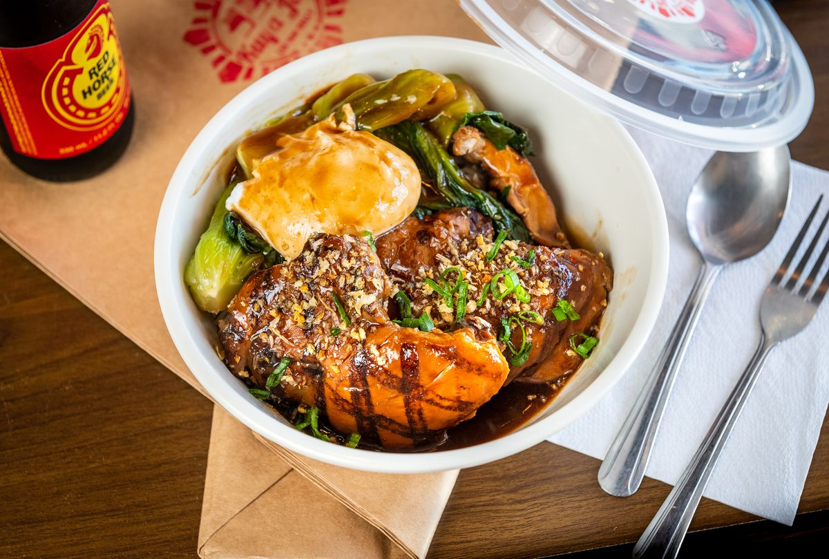 Boneless chicken thighs glazed in sweet soy sauce and topped with crushed peanuts go into a takeout bowl filled with bok choy and a poached egg.