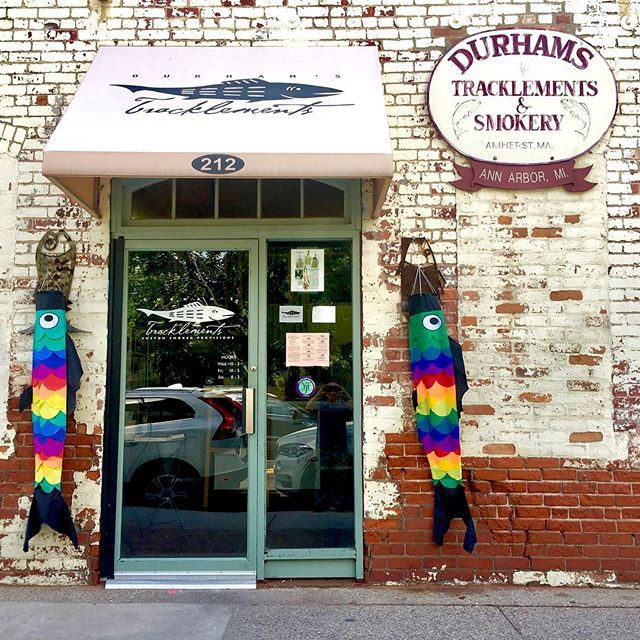 Two colorful fish kites hang beside the doors to Durham's.