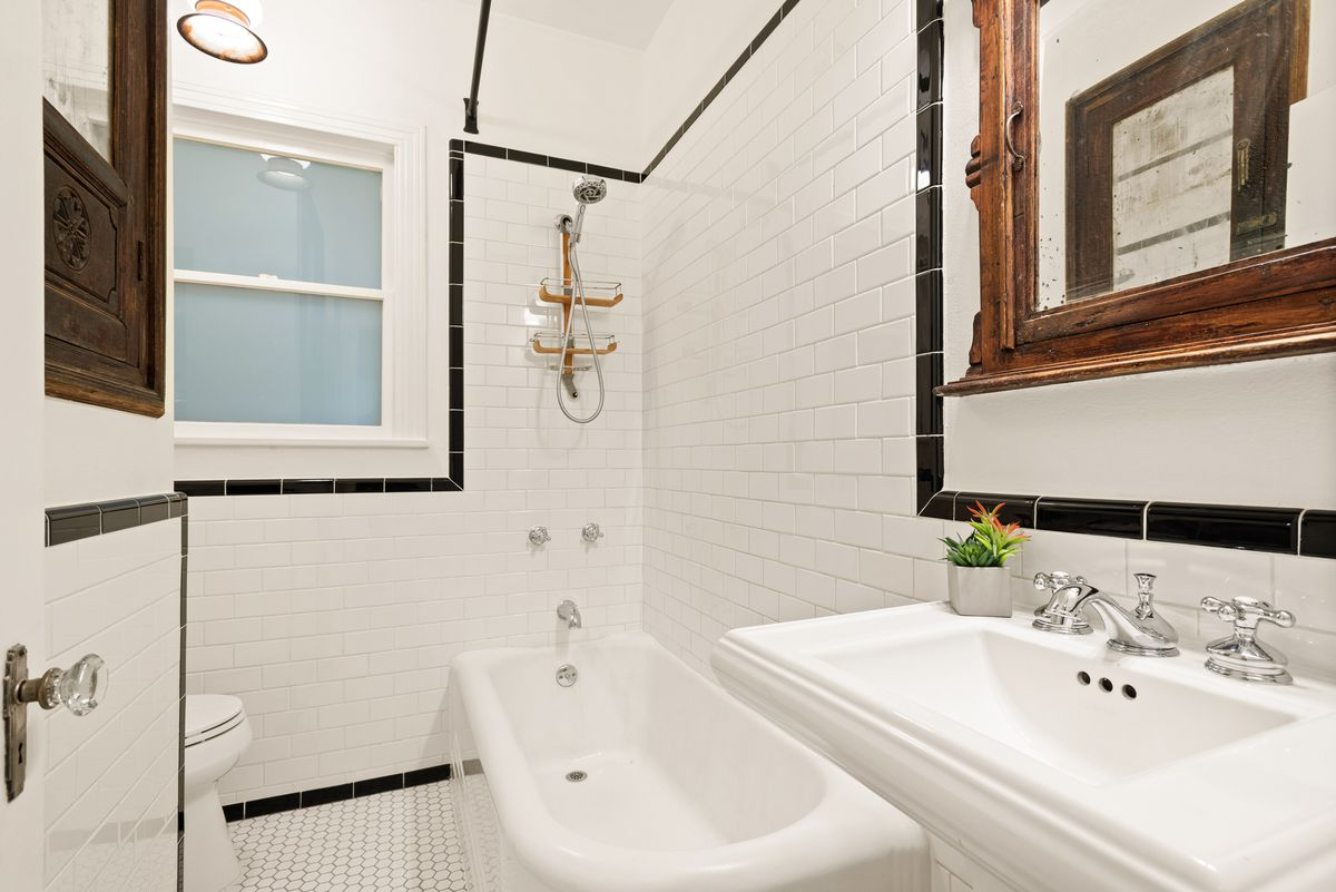 A bathroom with a door that has a crystal dooknob. There's penny tile on the floor and subway tile on the walls. There's a rectangular pedestal sink under a wood-framed mirror in front. There's a small double-hung window  above the toilet in back.