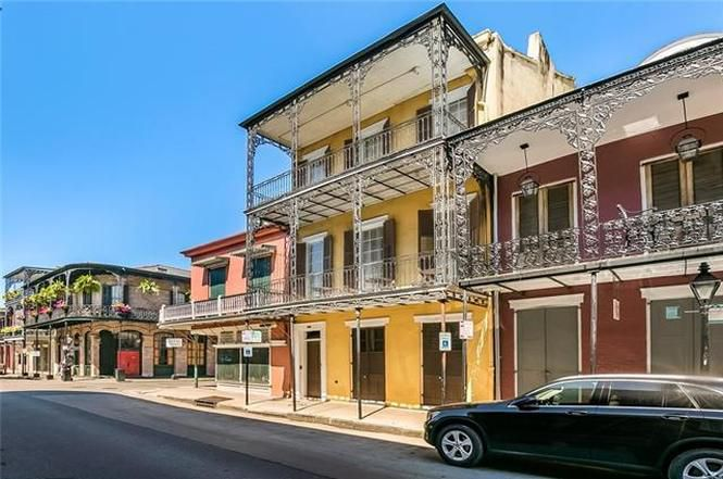 The exterior of 1103 Royal Street in New Orleans. The facade is yellow and there are multiple balconies on the upper levels. The roof is flat.