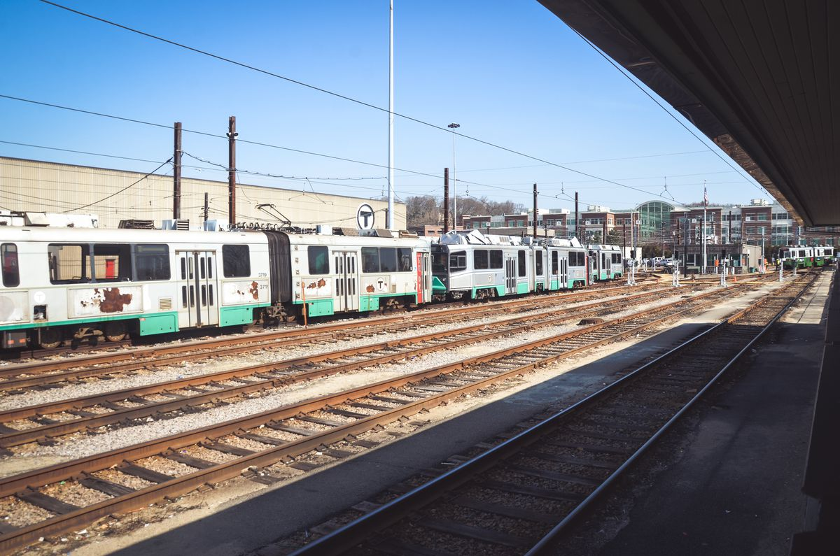 A subway train parked next to two lines of empty track.