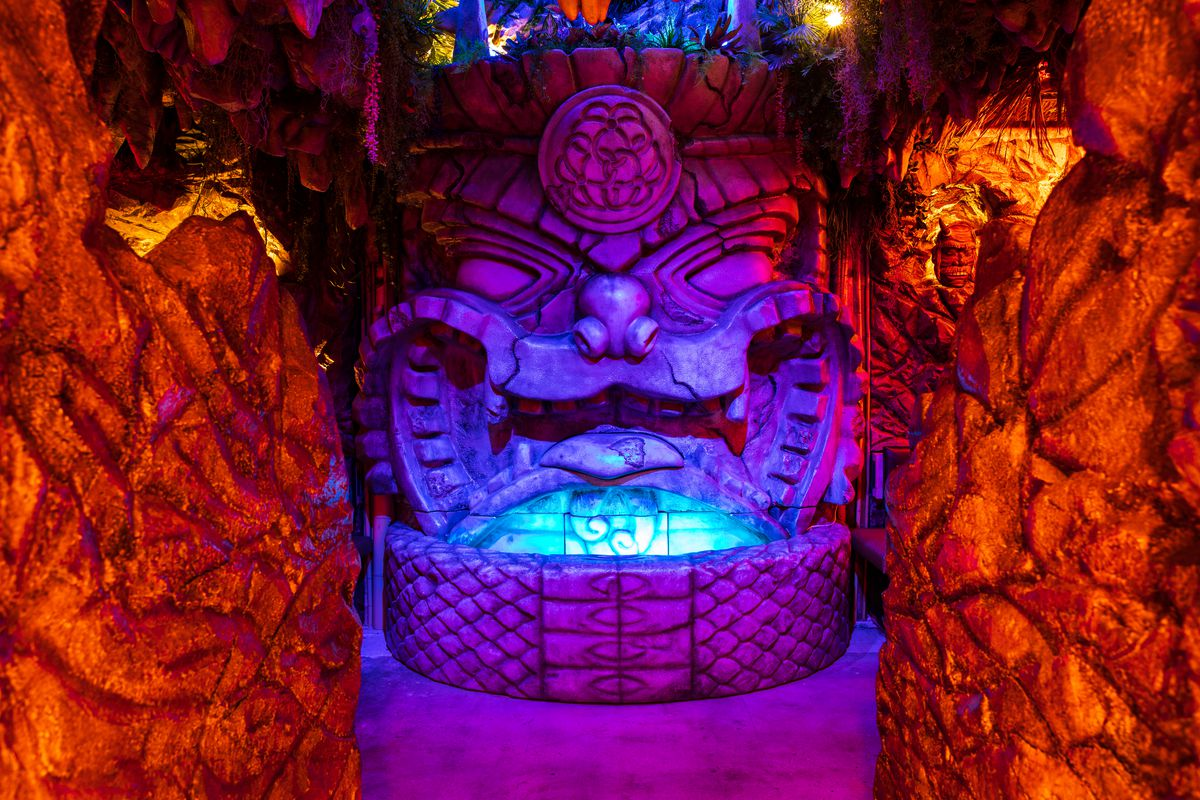 A shisa dragon fountain awash in dramatic purple and blue light.