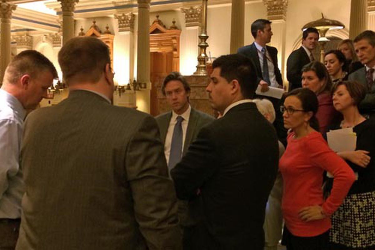Sen. Mike Johnston (center, facing camera) talks with lobbyists and senators.