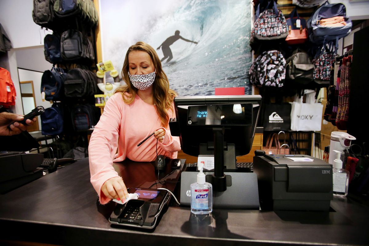 Liz Atkinson, manager of the Quicksilver store at the Outlets at Traverse Mountain in Lehi, cleans a terminal after a transaction on Friday, May 1, 2020.