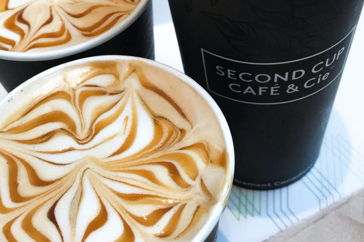 three cardboard cups of latte with caramel drizzle