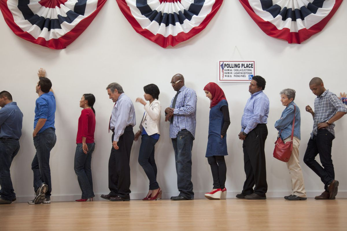 People wait in line to vote at a polling station, with red, white, and blue banners hanging above them.