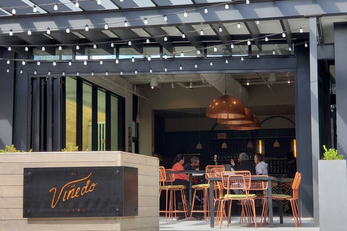 The patio at El Vinedo Local in Midtown Atlanta with orange metal chairs and wood tables. A dark metal sign etched with the El Vinedo Local wraps around the wooden wall entrance to the restaurant patio