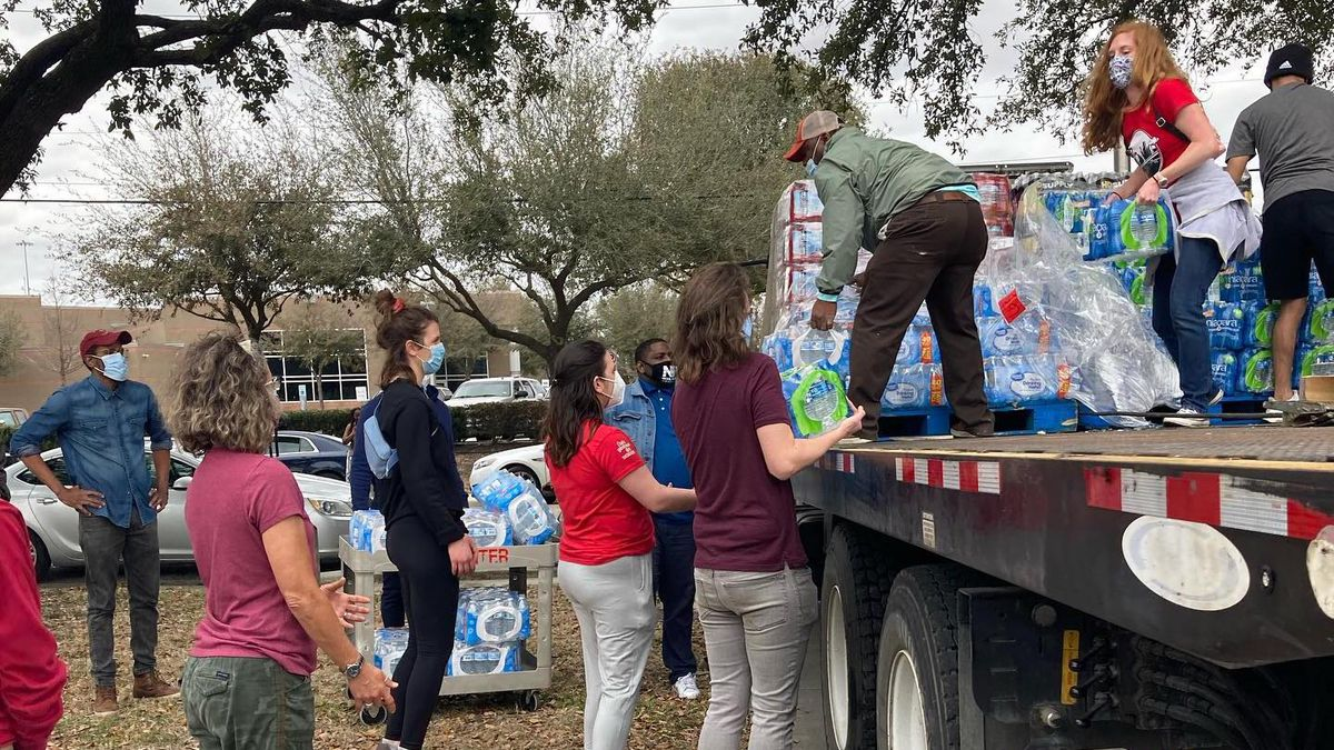 A group of people stands on the back of a flatbed trailer handing out cases of bottled water