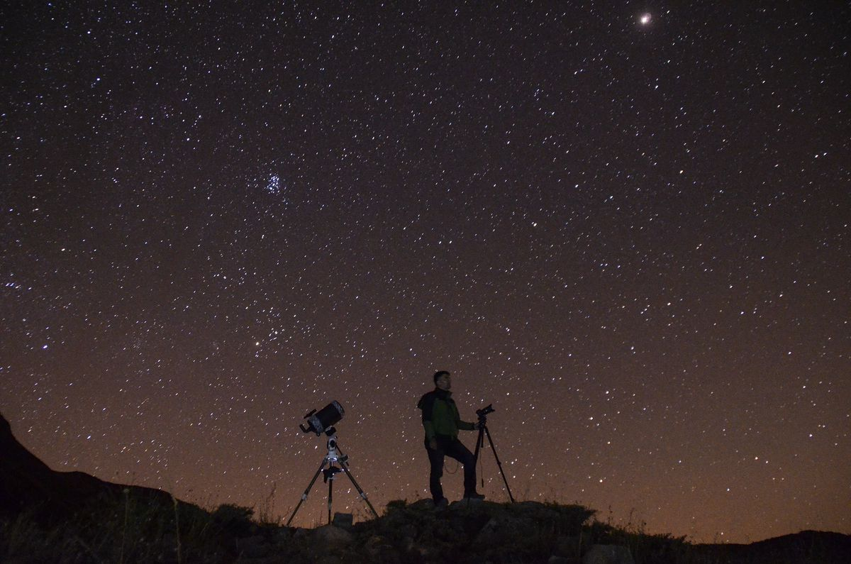 A person with two cameras on tripods stands on a hilltop at night with the starry sky behind them.