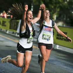 Kirra Morgan and Teos Jackson cheer as they cross the finish line of the Deseret News Half Marathon in Salt Lake City on Friday, July 23, 2021.