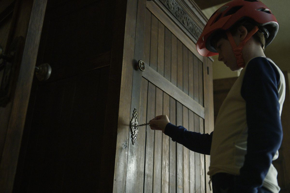 Bode Locke, in a bike helmet to protect against dangers, inserts an elaborate key into the lock on a tall wardrobe.