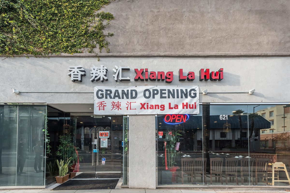 Signage for a grand opening of a restaurant called Xiang La Hui, shown in a red sign.