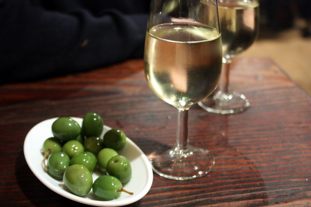 A glass of sherry sits next to a small plate of olives on a wood bar with someone leaning nearby.