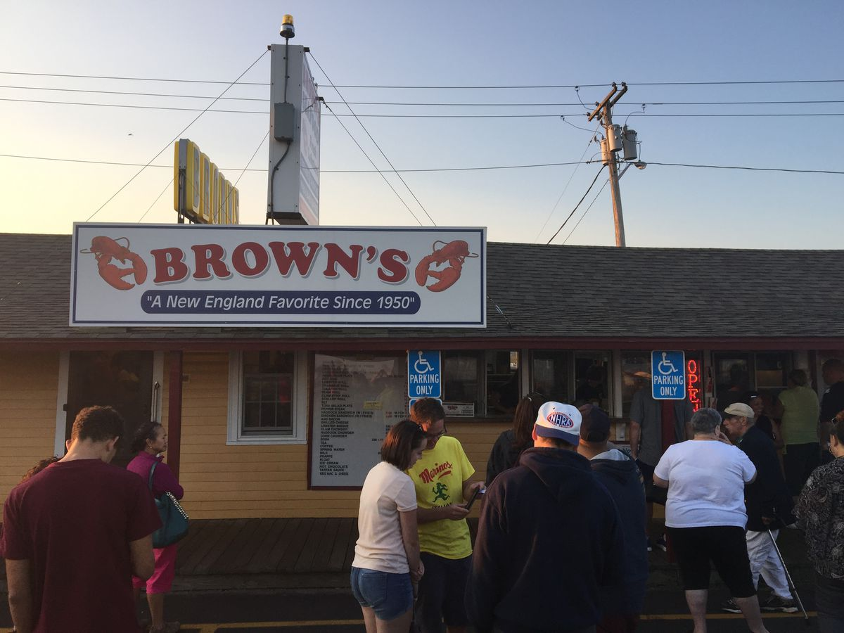 """People in summer clothing mill about in a parking lot in front of a casual restaurant exterior with signage reading """"Brown's"""""""