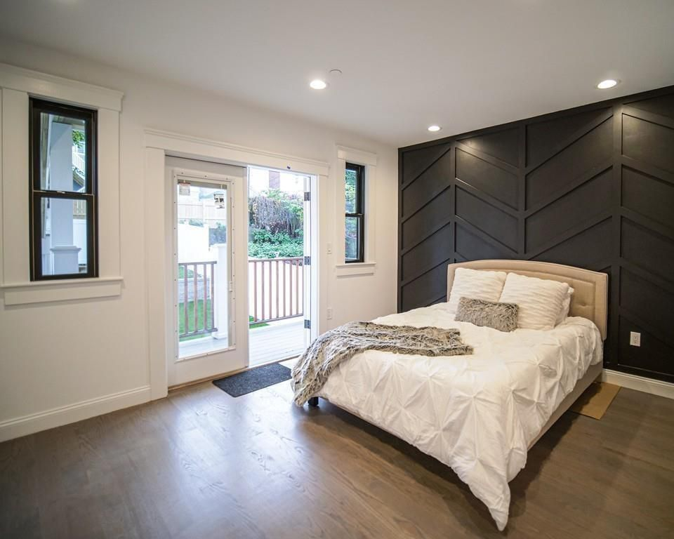 A bedroom with a bed next to a glass door leading to a small terrace.