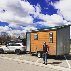 Ivor stands next to his tiny house, named Tad Cooper.