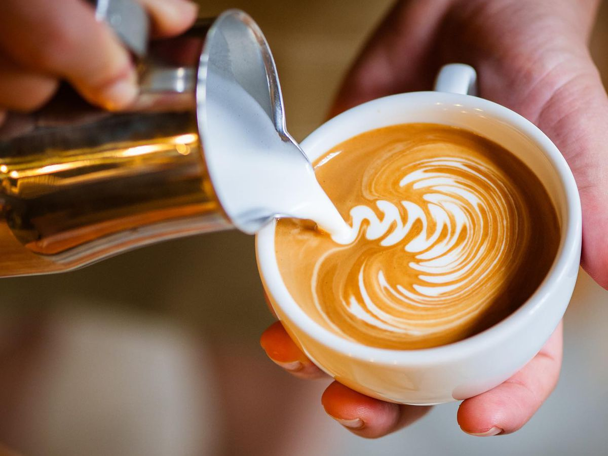 A hand holding a white cup with latte and another hand pouring cream.