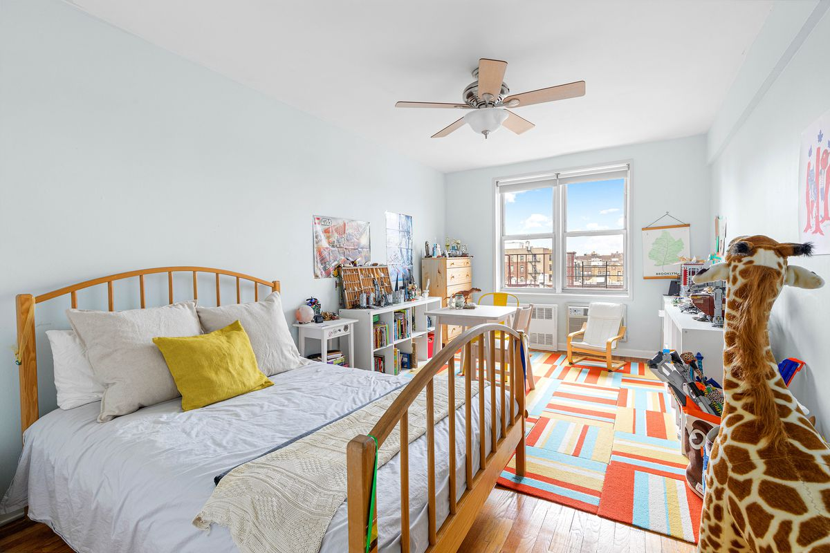 A large bedroom with a bed, a colorful rug, and a toy giraffe.