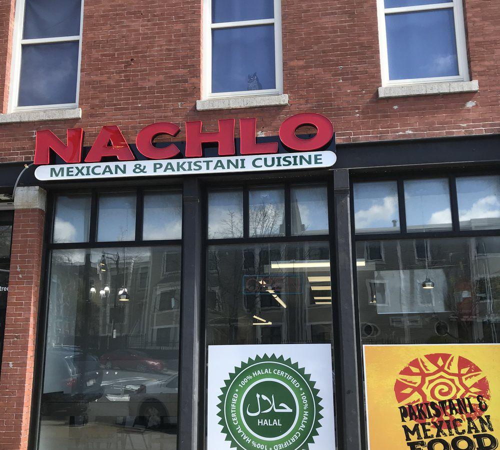 """A casual restaurant exterior on the ground floor of a brick building has signage that reads """"Nachlo: Mexican & Pakistani Cuisine."""" There's also halal signage."""