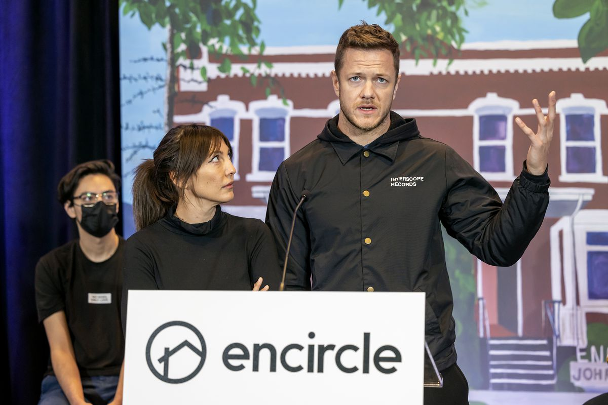 Aja Volkman, lead singer for Nico Vega, looks up at her husband, Dan Reynolds, lead singer of Imagine Dragons, as Reynolds speaks during a press conference for Encircle at the Silicon Slopes Summit at the Salt Palace in Salt Lake City on Wednesday.