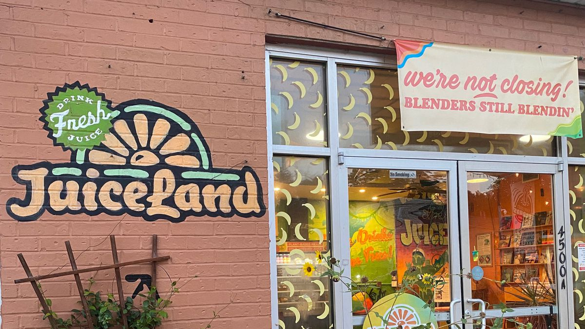 """Above glass doors decorated with banana stickers hangs a banner reading, """"We're not closing! Blenders still blendin."""""""