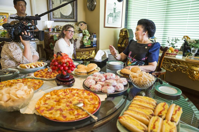 """Lauren Greenfield interviewing Imelda Marcos for the documentary """"The Kingmaker."""" Greenfield, Marcos, and the camera operator all sit at a table covered with dishes of food."""