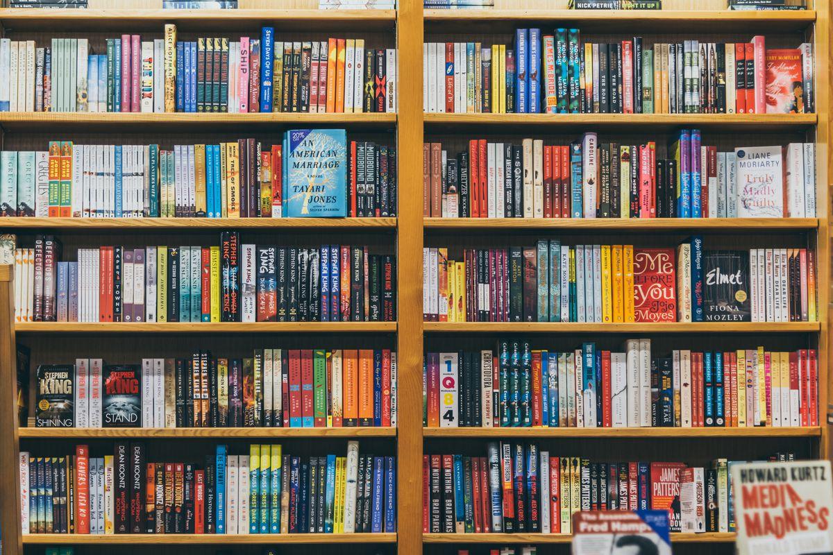 A wooden shelf of books in a bookstore.