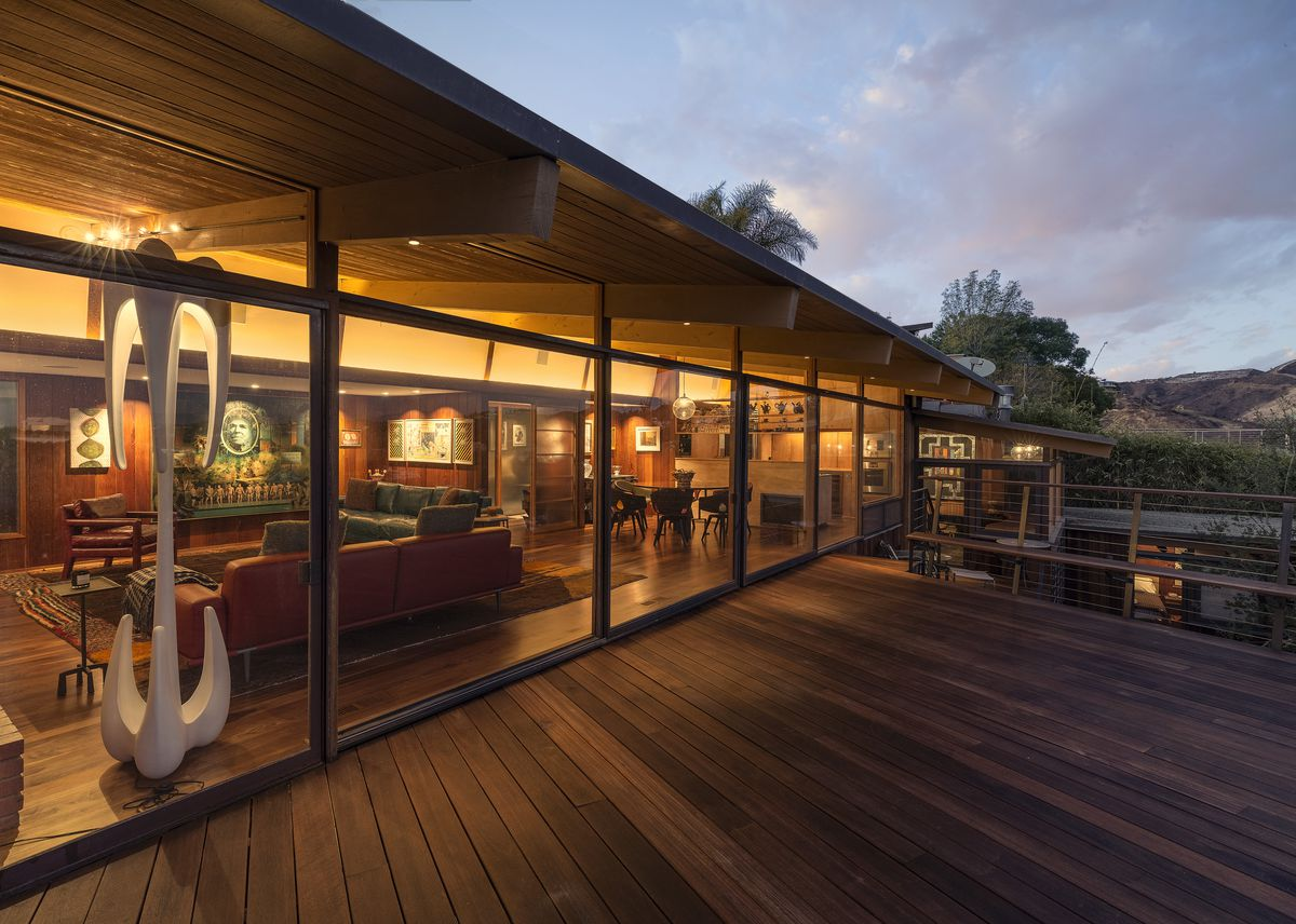 A wood deck extends from an expanse of glass walls along the side of the home.