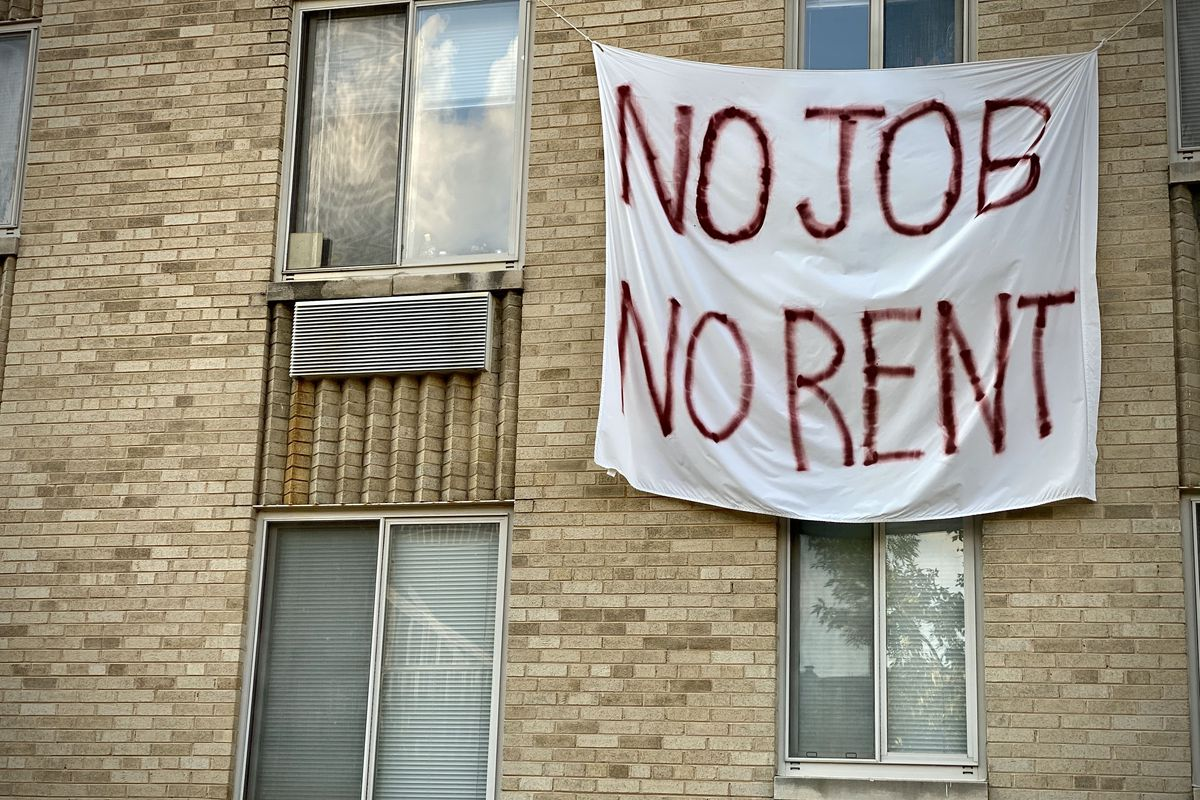"""A banner reading """"No job no rent"""" on an apartment building."""